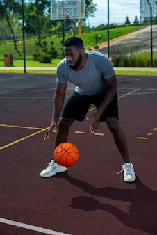Uomo bello americano che gioca a pallacanestro a distanza