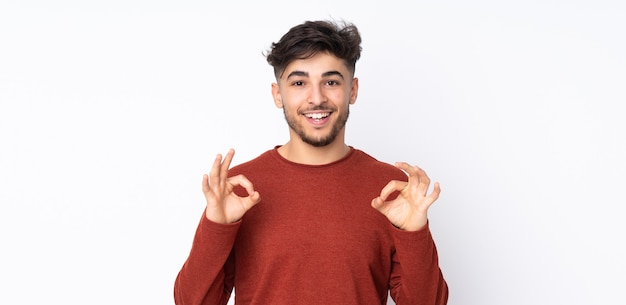 Uomo bello arabo isolato che mostra segno giusto con due mani