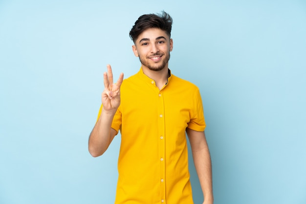 Uomo bello arabo sopra la parete felice e contando tre con le dita