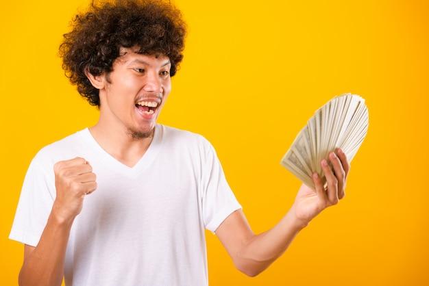 Uomo bello asiatico con capelli ricci che tengono le banconote in dollari