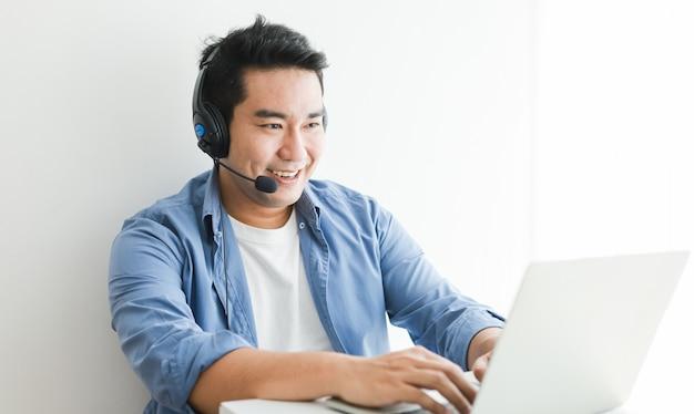 Uomo bello asiatico in camicia blu facendo uso del computer portatile con il sorriso di conversazione della cuffia e il fronte felice