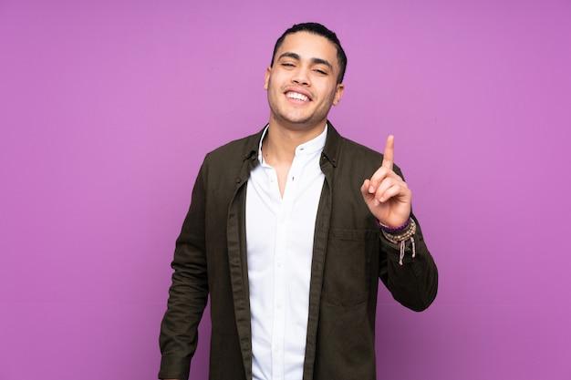 Uomo bello asiatico sulla parete blu che mostra e che solleva un dito in segno del meglio