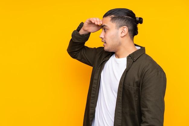 Uomo bello asiatico sulla parete gialla che mostra segno giusto con le dita