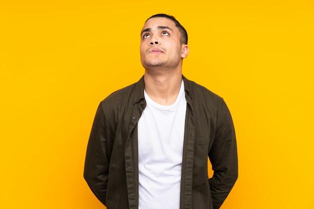 Uomo bello asiatico sulla parete gialla che pensa un'idea