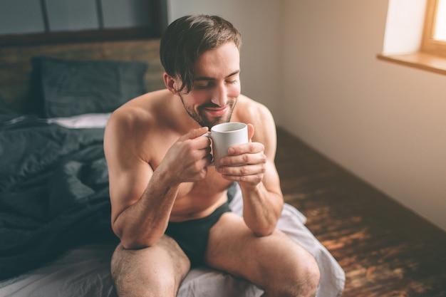 Uomo bello barbuto nudo con i capelli scuri che tiene una tazza di tè o caffè caldo nella sua camera da letto. è mattina.