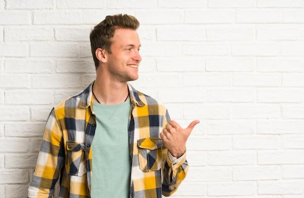 Uomo bello biondo sopra il muro di mattoni bianco che indica il dito sul lato