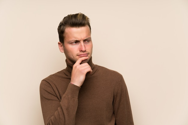 Uomo bello biondo sopra la parete isolata che pensa un'idea