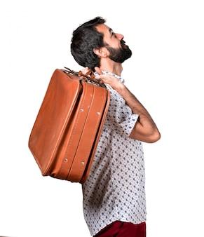 Uomo bello brunetta con la barba che tiene una valigetta d'annata