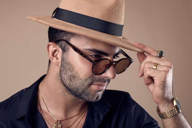 Uomo bello brutale abbronzato hipster in camicia nera, cappello e occhiali