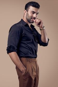 Uomo bello brutale abbronzato hipster in camicia nera e occhiali