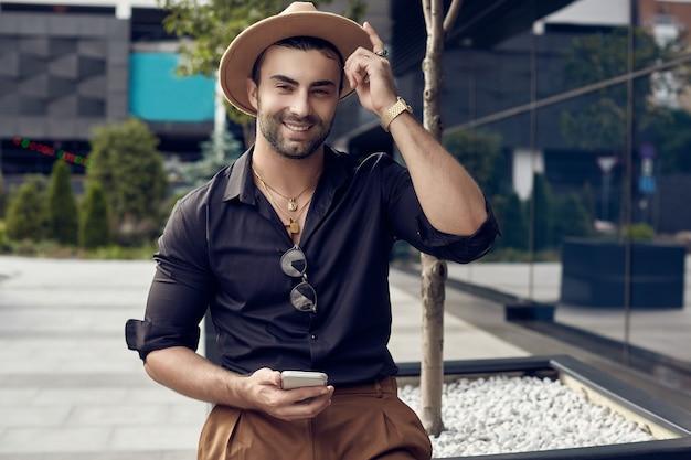 Uomo bello brutale abbronzato muscoloso hipster in camicia e cappello neri con il telefono