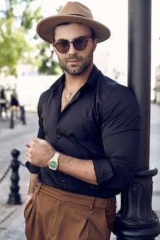 Uomo bello brutale abbronzato muscoloso hipster in posa per le strade