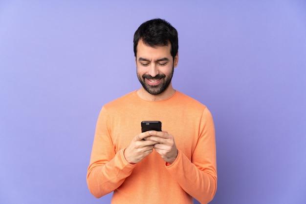 Uomo bello caucasico che invia un messaggio con il cellulare