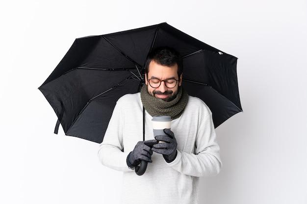 Uomo bello caucasico con la barba che tiene un ombrello e un caffè da portare via