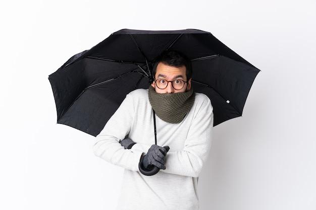 Uomo bello caucasico con la barba che tiene un ombrello