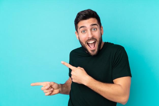 Uomo bello caucasico isolato sul lato blu sorpreso e indicante della parete