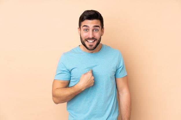 Uomo bello caucasico isolato sulla parete beige con espressione facciale di sorpresa
