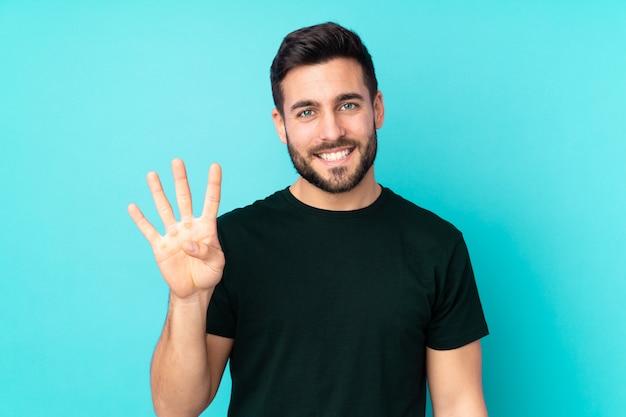 Uomo bello caucasico isolato sulla parete blu felice e contando quattro con le dita
