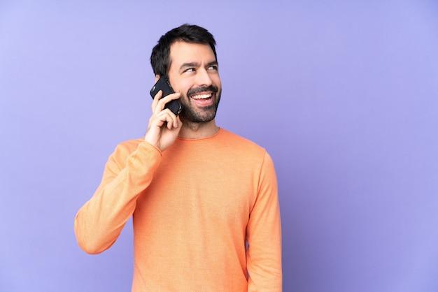 Uomo bello caucasico sopra la parete viola isolata che mantiene una conversazione con il telefono mobile