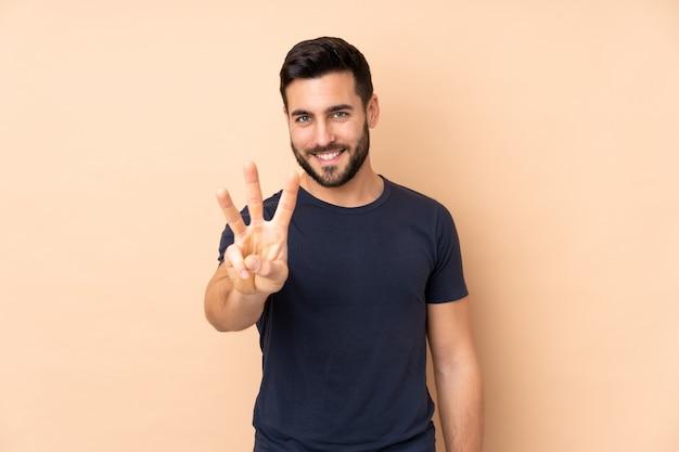 Uomo bello caucasico sulla parete beige felice e contando tre con le dita