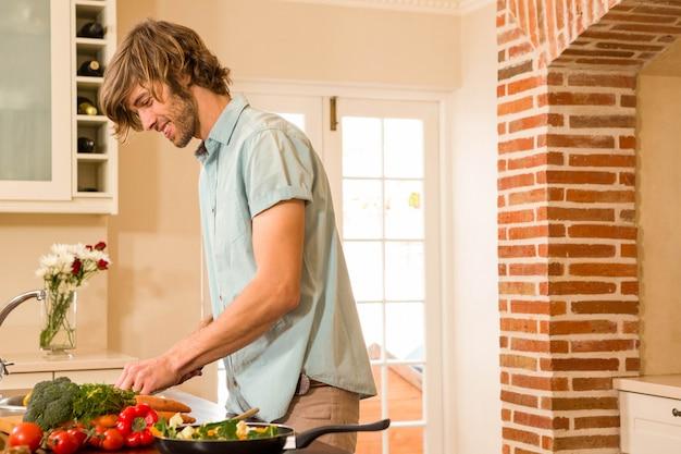 Uomo bello che affetta le verdure nella cucina