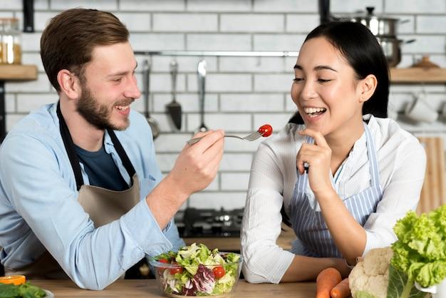 Uomo bello che alimenta pomodoro allegro a sua moglie in cucina