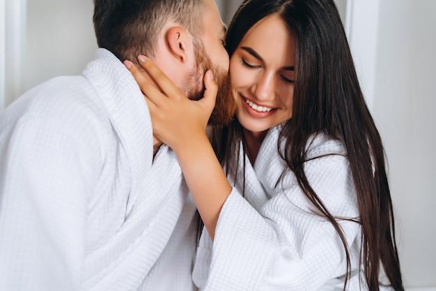 Uomo bello che bacia bella donna sulla guancia mentre