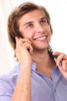 Uomo bello che chiama dal telefono cellulare