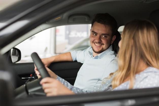 Uomo bello che esamina driver femminile