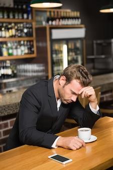 Uomo bello che esamina smartphone e che mangia un caffè