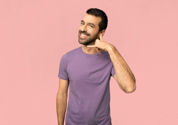 Uomo bello che fa gesto del telefono. chiamami indietro segno su sfondo rosa isolato