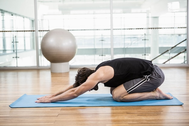 Uomo bello che fa yoga sulla stuoia in studio