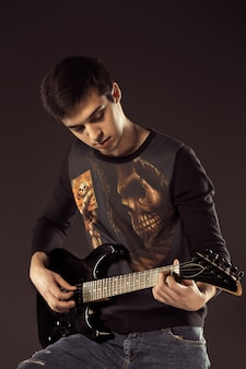 Uomo bello che gioca elettro chitarra, colpo