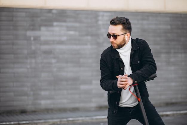 Uomo bello che guida in città su scooter