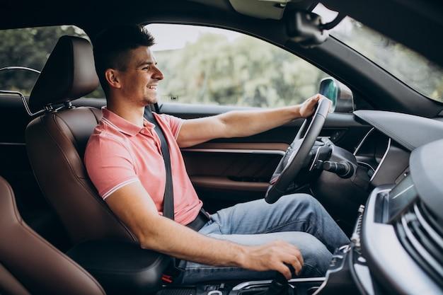 Uomo bello che guida in sua automobile