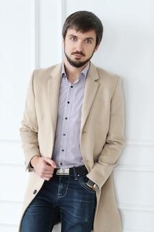 Uomo bello che indossa cappotto beige