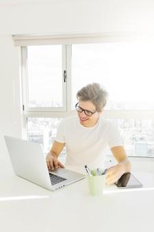 Uomo bello che lavora al computer portatile a casa