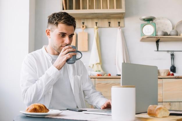 Uomo bello che lavora al computer portatile che beve caffè in cucina