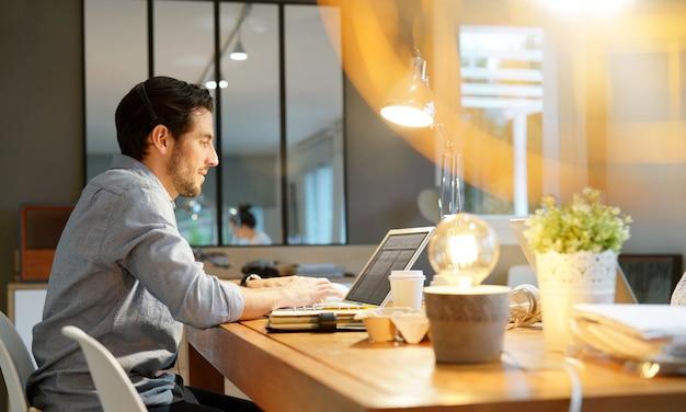 Uomo bello che lavora al computer portatile in co spazio di lavoro