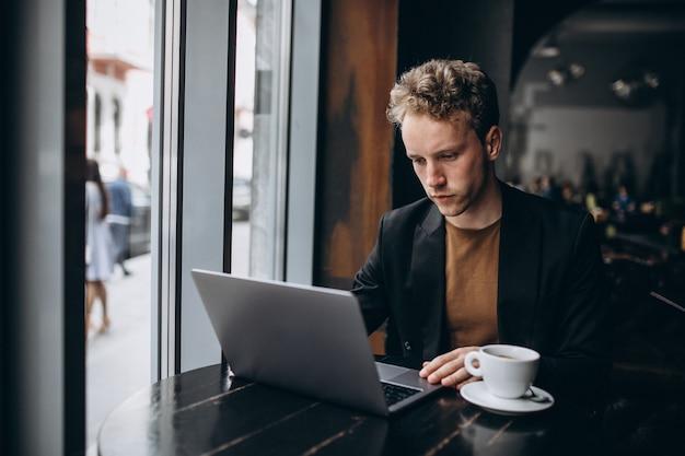 Uomo bello che lavora su un computer in un caffè e bere caffè
