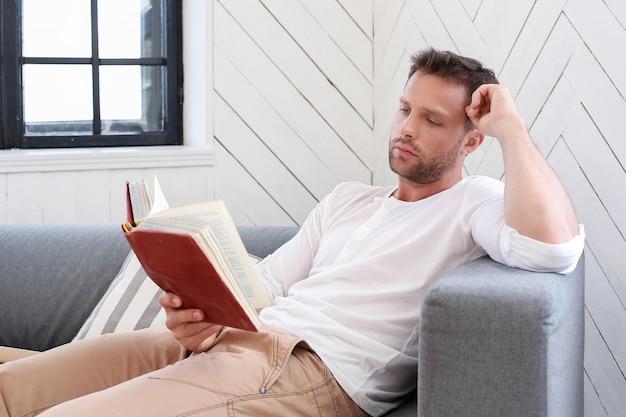 Uomo bello che legge un libro nel sofà