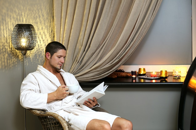 Uomo bello che legge un libro