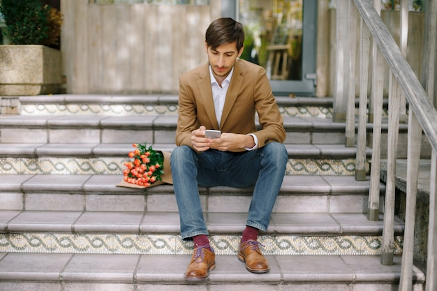Uomo bello che manda un sms mentre esaminando il telefono