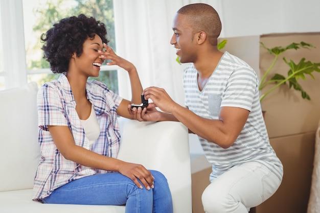 Uomo bello che offre l'anello di fidanzamento alla sua ragazza nel soggiorno
