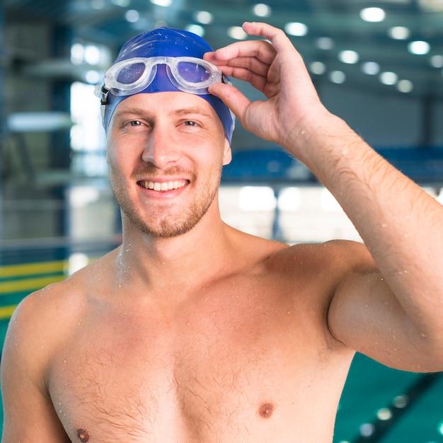 Uomo bello che organizza i suoi occhiali da nuoto