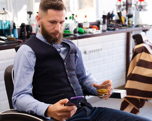 Uomo bello che osserva sul suo telefono il negozio di barbiere