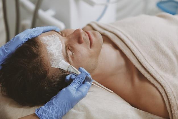Uomo bello che ottiene trattamento facciale di cura della pelle
