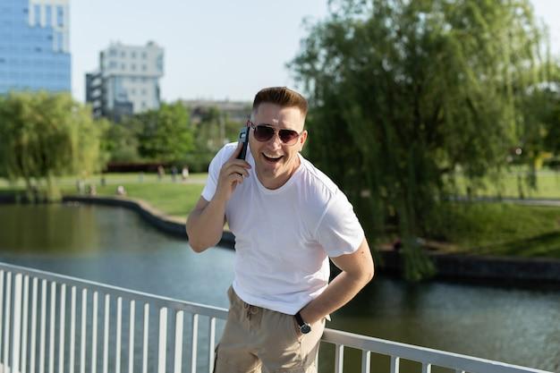 Uomo bello che parla al telefono nel parco