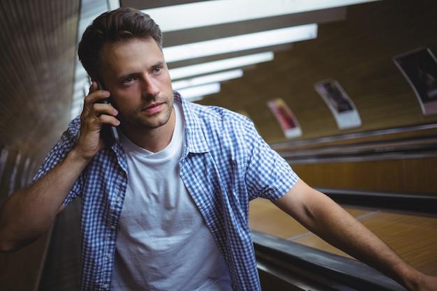 Uomo bello che parla sul telefono cellulare sulla scala mobile
