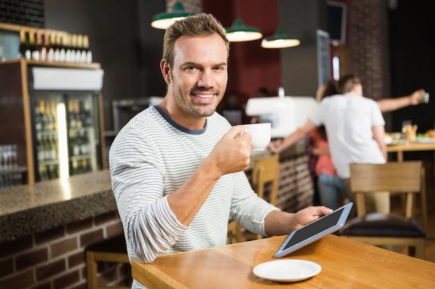 Uomo bello che per mezzo del computer della compressa e mangiando un caffè